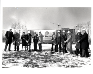 11 men and women in winter coats with shovel at a ceremonial ground breaking for AT&T