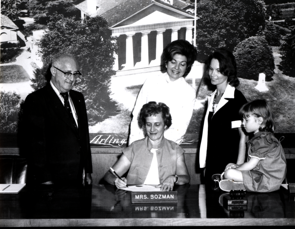 Ellen Bozman working in the County Board office, surrounded by an unidentified man, two women and a child sitting on the desk.